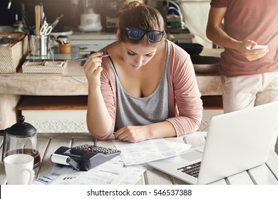 Family budget and financial problems. Concentrated worried woman doing paperwork at home, calculating domestic expenses and paying gas and electricity bills, using laptop computer and calculator
