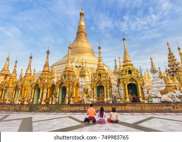 family burmese people  praying respects at Shwedagon big golden pagoda most sacred Buddhist pagoda in rangoon, Myanmar(Burma) on blue sky background