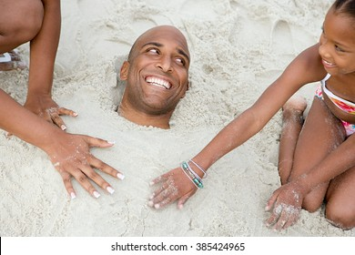 Family burying father in sand