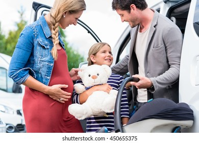 Family buying car, mother, father and child at dealership with soft toy and special kid seat