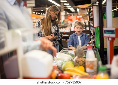 Family buying food: portrait of happy young woman watching her son laying groceries on cashiers desk in supermarket