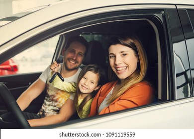 Family buying a new car in the car dealership saloon.