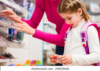 Family buying school supplies in stationery store, little girl looking at a fountain pen