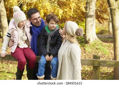 Family By Wooden Fence On Autumn Walk