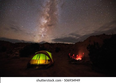 Family camping under the Milky Way with a campfire and glowing tent, Escalante, Utah, USA.