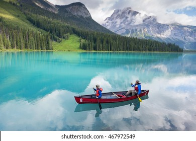 family canoeing on emerald lake