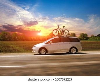 Family car with the bycycle on the highway