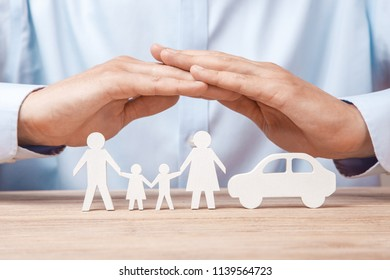 Family and car insurance. Man in  shirt covers his family with his father, mother, son and daughter and  car.