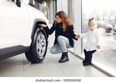 Family in a car salon. Mother with daughter. Lady in a black jacket.