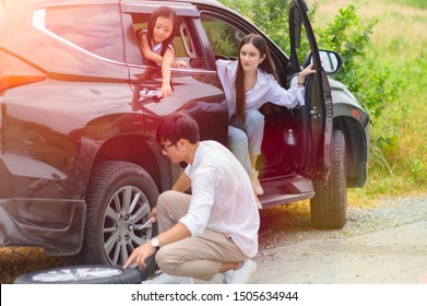 family in car tire flat during traveling, finish tire replacement by leader father, cheerfully at the end