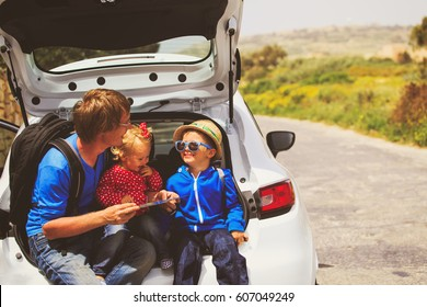 family car travel - father with two kids looking at map on road