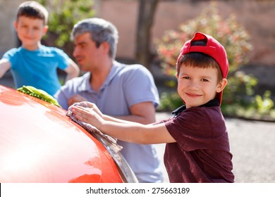 Family car wash day, little boy cleaning spotlight, father and brother in background out of focus