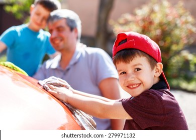 Family car wash, little boy cleaning spotlight, father and brother in background