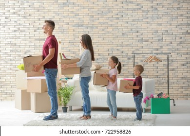 Family with cardboard boxes standing in row at home