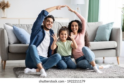 Family care. Arabic parents making symbolic roof of hands above cute little daughter while sitting together on floor in living room, middle eastern mom and dad having fun with their child at home