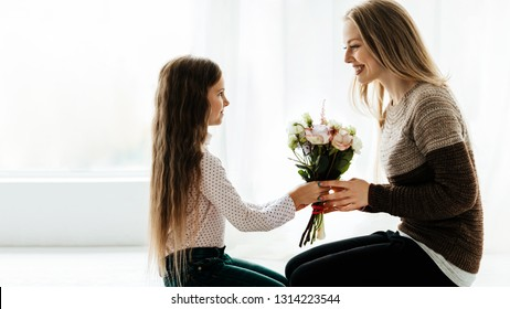 Family. Care. Holiday. Mom and daughter. Cute little girl is giving her mom a bouquet, both are smiling; at home