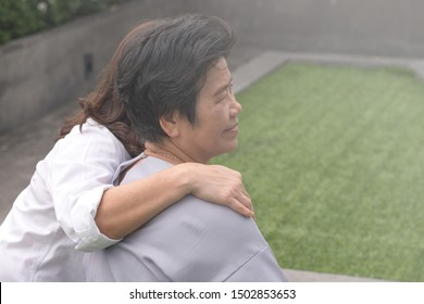 Family caregivers lifestyle concept. Asia older female mother and Asian daughter together in garden.