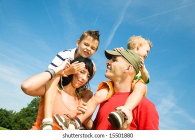 Family carrying their two sons on their shoulders under a perfect sky