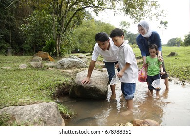 family catching fish at the stream