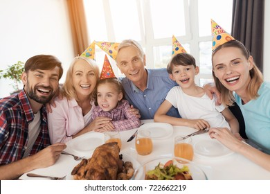 The family celebrates the birthday of a little girl. Happy girl is sitting in the center of the table. Her relatives in holiday caps are sitting around her and smiling