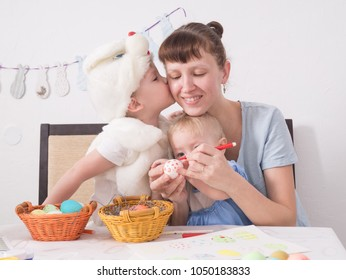 The family celebrates the Passover: Mom paints a pattern on the Easter egg. The son kisses his mother on the cheek. Portrait
