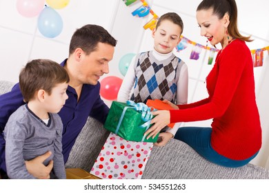 Family celebrating a birthday opening gifts in living room.