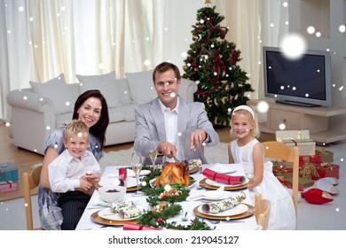 Family celebrating Christmas dinner with turkey against snow