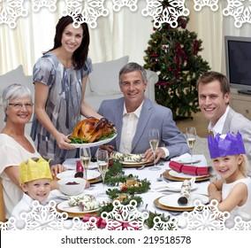 Family celebrating Christmas dinner with turkey against snowflake frame