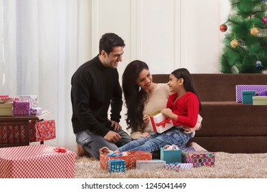 Family Celebrating Christmas with Gifts at home