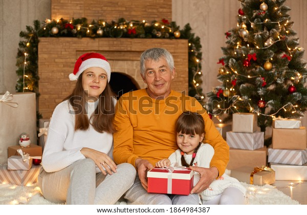 Family celebrating Christmas at home with lots of gifts, mommy with daughter and grandfather sitting in living room on floor against xmas tree and fireplace, look at camera, wear casually.