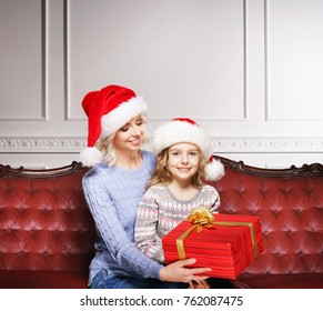 Family celebrating Christmas at home. Mother and daughter with holiday gifts. Xmas concept.