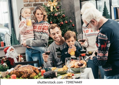 family celebrating christmas together while grandpa pouring wine into glass