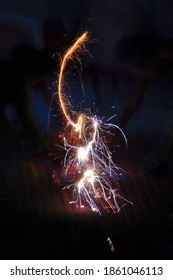Family celebrating the festival of Diwali with a sparkler, India (portrait)
