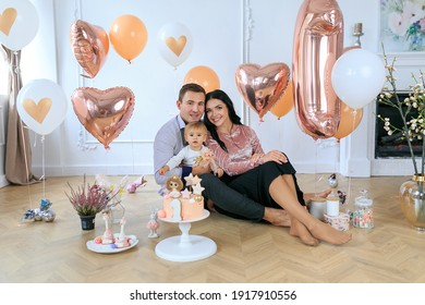 Family celebrating first birthday party their daughters. Cute girl celebrating 1st birthday with dad and mom at home. Party decor, cake, sweets, balloons. daughter with parents children's holiday