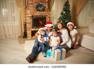 family celebrating at home. father, mother and children on the background of the fireplace and Christmas tree. New Year and xmas people