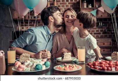 Family celebrating mother's birthday in decorated kitchen. Beautiful woman is looking at camera and smiling while husband and son are kissing her in cheeks