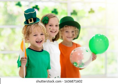 Family celebrating St. Patrick's Day. Irish holiday, culture and tradition. Kids wear green leprechaun hat and beard with Ireland flag and clover leaf. Children having fun at St Patrick party. - Shutterstock ID 1636871602