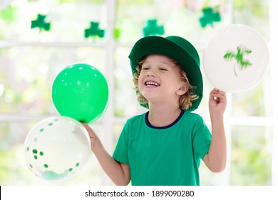 Family celebrating St. Patrick's Day. Irish holiday, culture and tradition. Kids wear green leprechaun hat and beard with Ireland flag and clover leaf. Children having fun at St Patrick party. - Shutterstock ID 1899090280