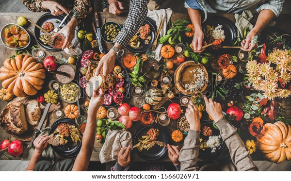 Family celebrating Thanksgiving day. Flat-lay of eating and drinking peoples hands over Friendsgiving table with traditional Fall food, roasted turkey, candles, pumpkin pie, top view