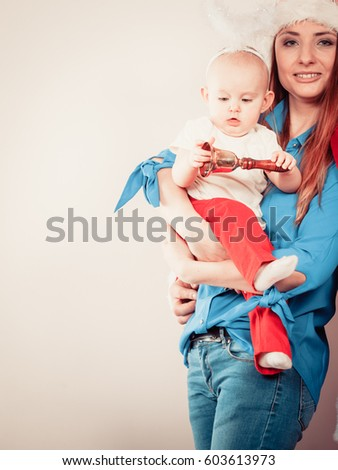 9ab687a1f5830 Family celebration concept. Christmas woman with cute baby. Beautiful lady  has red santa claus