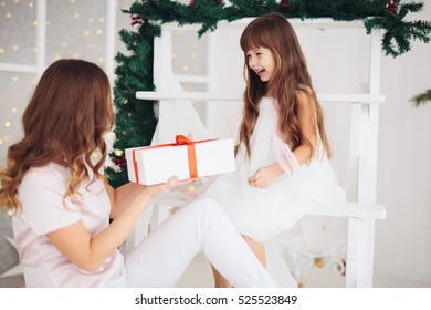 Family celebration of the New Year. The mother and little daughter celebrates Christmas. Holiday and fun.