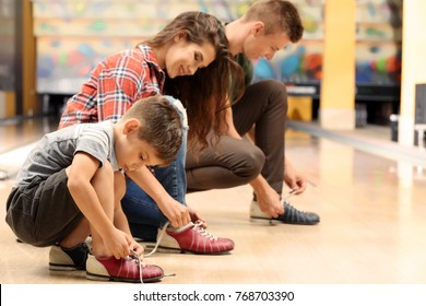Family changing their shoes in bowling club