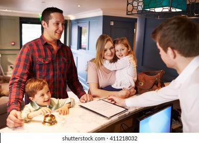 Family Checking In At Hotel Reception Desk