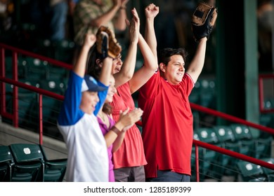 Family cheering on a baseball game at a sports stadium.