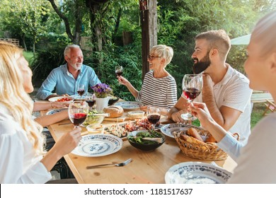 Family cheering over the dining table outdoors, celebration