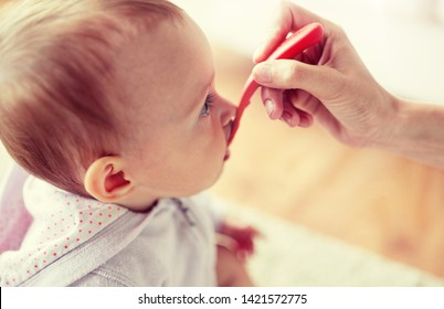 family, child, eating and people concept - close up of hand with spoon feeding little baby at home