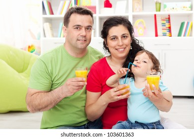 Family with child having fresh fruit juice at home