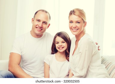 family, child and home concept - smiling parents and little girl at home
