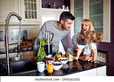 Family with child in kitchen having breakfast
