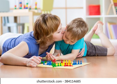 Family child and mom playing board game at home on the floor at home